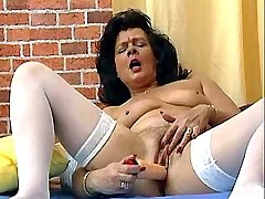 Middleaged brunette maid fucks herself w dildo in bed